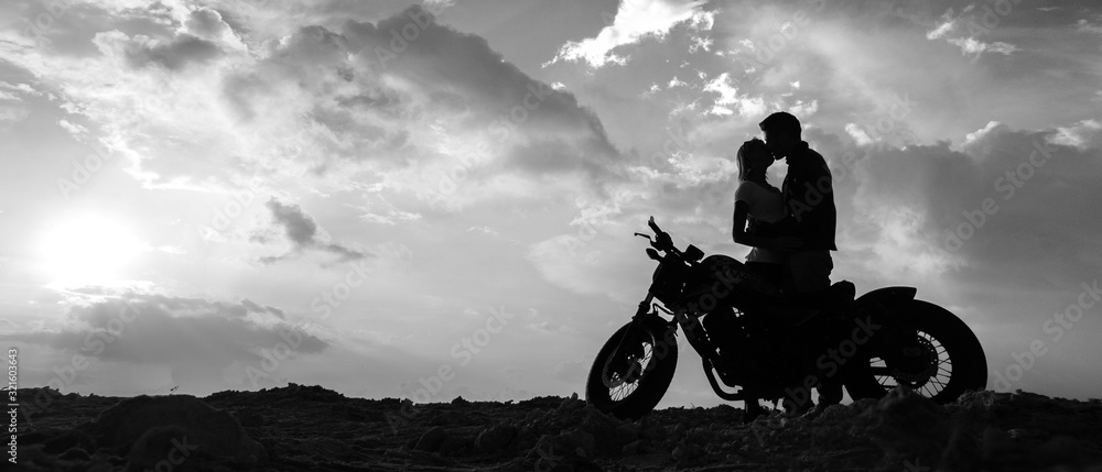 Fototapeta Silhouettes of a couple in love with a motorcycle on the background of the sunset sky