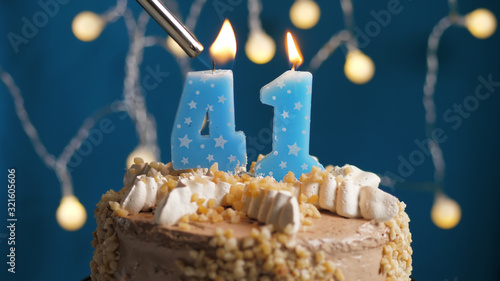 Tela Birthday cake with 41 number candle on blue backgraund set on fire by lighter