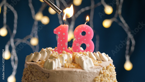 Photo Birthday cake with 18 number candle on blue backgraund set on fire by lighter
