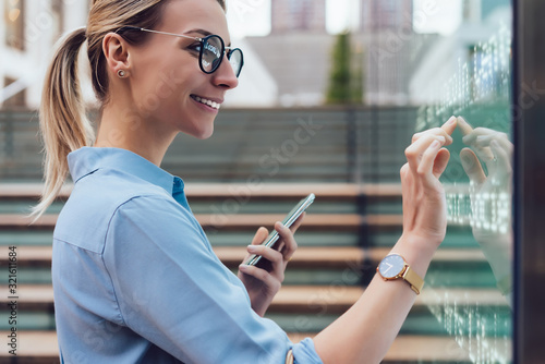 Obraz Interactive digital kiosk with public transport Info. Smiling female standing at big display with smartphone in hand.Young woman touching with finger interactive futuristic screen. Advanced technology - fototapety do salonu