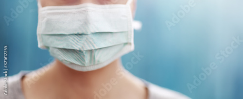 Canvastavla young woman in medical face protection mask indoors on blue background