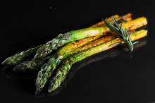 Grilled Asparagus On A Black Background With A Sprig Of Rosemary