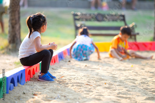 Obraz Little child girl sitting lonely watching friends play at the playground.The feeling was overlooked by other people. - fototapety do salonu