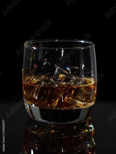 Whiskey splash in glass with ice on a dark background