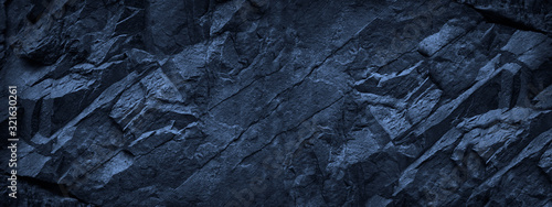 Fototapeta Dark blue grunge background. Deep blue stone background. Toned mountain texture close-up. Banner with copy space for your design. Volumetric rock background. obraz