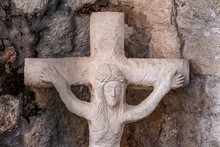 Closeup Ancient Statue Of Jesus Christ And The Crucifixion Made Of Gray Stone, Cracked Brick Wall Background