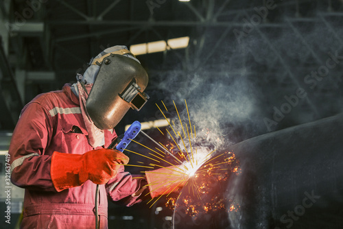 Metal workers use manual labor, skilled welder, factory workers making, welder is welding the steel pipe in factory, welding fumes, the welder standing to weld iron in dark tone Canvas-taulu