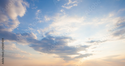 Blue sky clouds background. Beautiful landscape with clouds and orange sun on sky - 321647604
