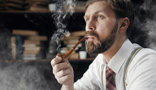 Portrait Of Thoughtful Bearded Mature Man Smoking Wooden Pipe Over Bookshelf Background