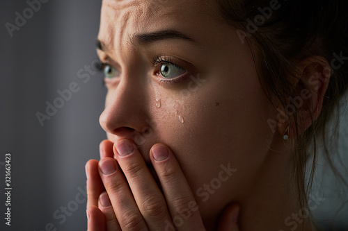 Foto Sad desperate crying female with folded hands and tears eyes during trouble, lif