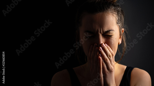 Sad desperate grieving crying woman with folded hands and tears eyes on a dark black background during trouble, life difficulties, loss and emotional problems Wallpaper Mural