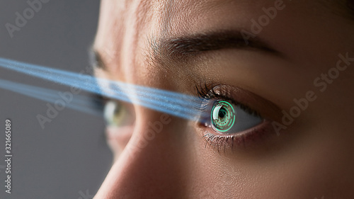 Obraz Female eye with smart contact lens with digital and biometric implants to scan the ocular retina close up. Future concept and high tech technology for scanning face id - fototapety do salonu