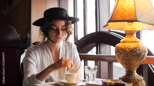 Portrait of a girl in a hat interfering with a spoon coffee at a cafe Fototapet