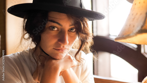 Fotografie, Tablou Portrait of a girl in black hat sitting in the cafe and posing for the camera