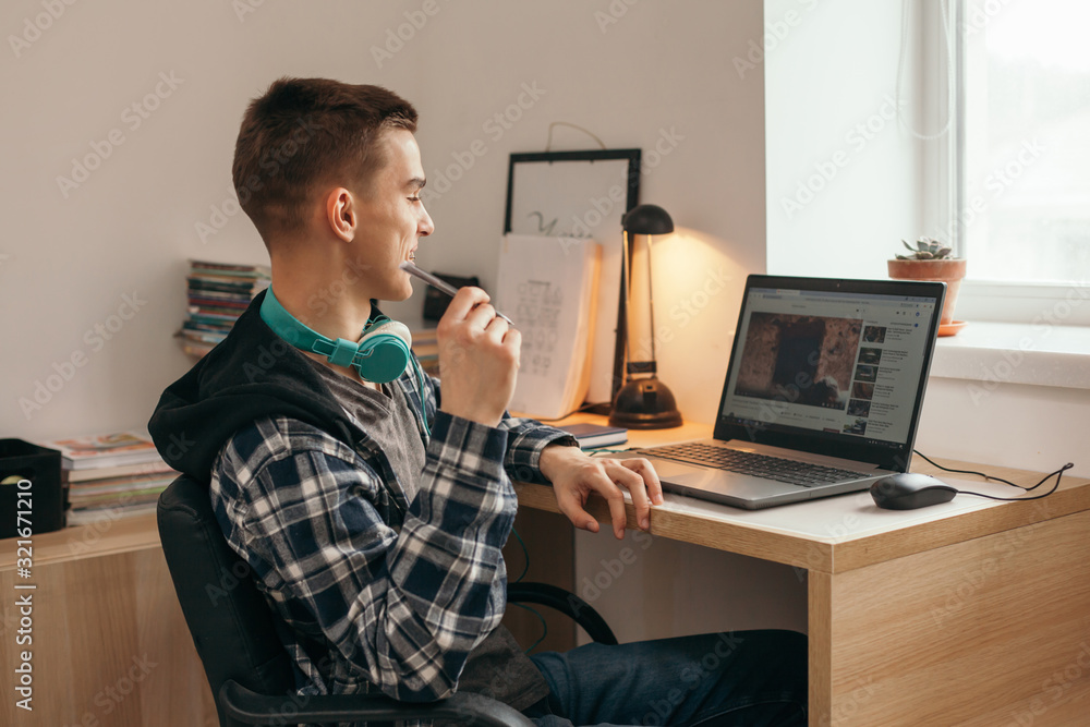 Fototapeta Teenage boy doing homework using computer sitting by desk in room alone