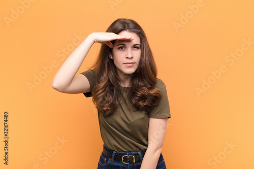young pretty woman looking bewildered and astonished, with hand over forehead lo Wallpaper Mural