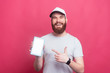 canvas print picture - happy smiling man with beard pointing at tablet screen over pink background