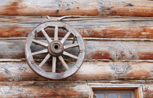 Wooden Wheel From A Cart On The Background Of A Wooden Log House