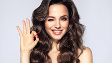 Girl With Curly Hair  Winking, Smiling And Showing OK Sign . Presenting Your Product. Makeup, Cosmetics And Beauty Products. Expressive Facial Expressions .