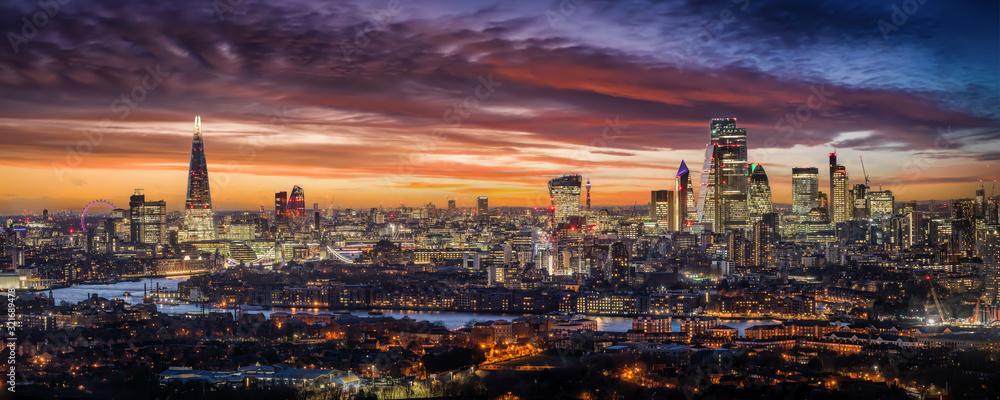 Fototapeta Weites Panorama der beleuchteten Skyline von London am Abend mit den Wolkenkratzern der City und zahlreichen Touristen Attraktionen, Großbritannien