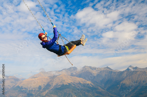 Fotografie, Obraz girl on a swing in the mountains is engaged in extreme sports