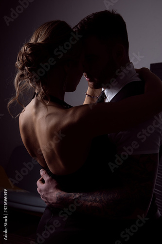 obraz PCV Passionate couple: a woman with a blonde hairdo wearing a black dress and a handsome unshaven man in a suit pose in a dark Studio