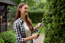 Female Gardener Pruning Bushes.
