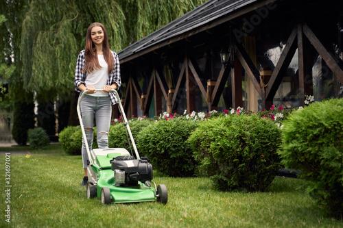 Slika na platnu Female gardener using lawn mower.