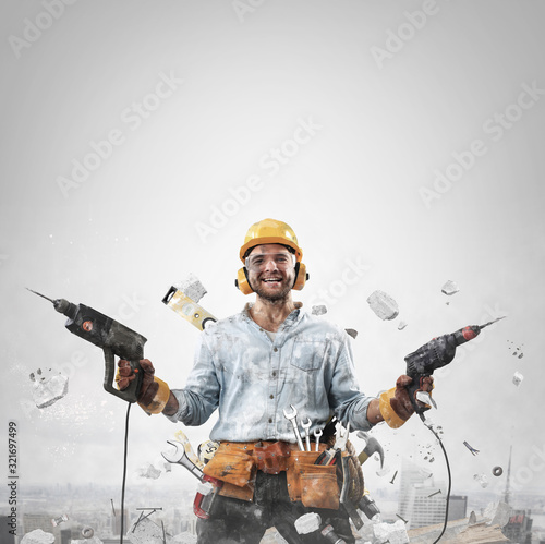 Fotografia Construction worker in dirty clothes with a hammer and drill at work