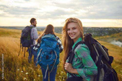Fototapeta Group of friends trekking with backpacks walking in the forest . obraz