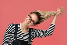 Young Girl Stretching Her Long Blond Dreads Standing Over Pink Background