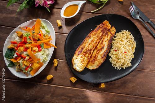 Photo Pescado a la plancha con especias y ensalada de lechuga zanahoria y aderezo mil