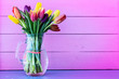 canvas print picture - Multicolored tulips in a vase on a pink background