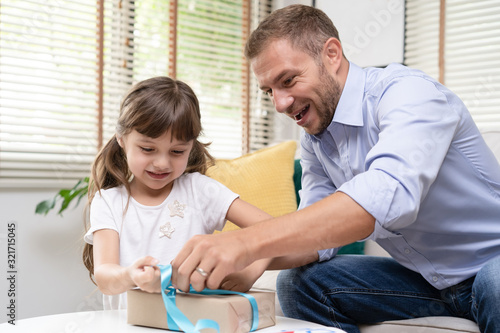 Cute daughter and her daddy help her to unwrap the gift box on Father's Day Canvas-taulu