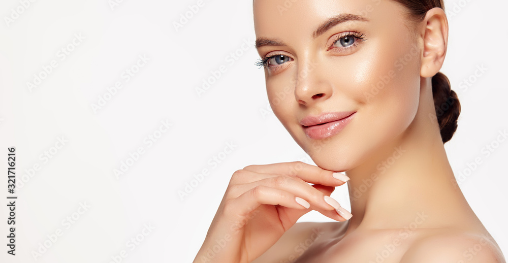 Fototapeta Beautiful young woman with clean fresh skin touching her face . Girl facial  treatment   . Cosmetology , beauty  and spa . Female  model, care concept