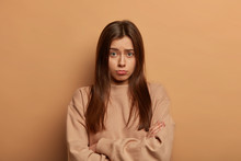 Gloomy Upset Insulted Woman Stands With Arms Folded, Feels Lonely And Wants To Cry, Being Betrayed By Close Person, Dressed Casually, Isolated On Beige Wall, Has Pitty Dissatisfied Face Expression