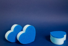 One And Two Blue Heart Shape Dishwash Spongenext To Each Other In The Foreground On The Blue Background