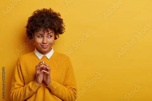 Fototapeta Photo of lovely woman steeps fingers, has genius great plan, evil intention, thinks over her scheme, looks aside with cunning expression, wears yellow sweater, stands indoor, copy space right obraz