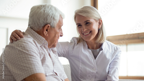 obraz PCV Smiling middle-aged nurse support comfort sick senior male patient