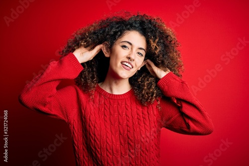 Young beautiful woman with curly hair and piercing wearing casual red sweater Smiling pulling ears with fingers, funny gesture Canvas Print