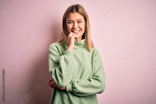 Fotografie, Tablou Young beautiful blonde woman wearing winter wool sweater over pink isolated background looking confident at the camera with smile with crossed arms and hand raised on chin
