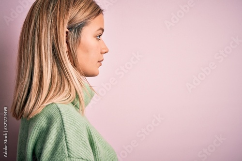 Fototapeta Young beautiful blonde woman wearing winter wool sweater over pink isolated background looking to side, relax profile pose with natural face with confident smile