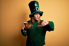 Young Beautiful Woman Wearing Green Hat Drinking Glass Of Beer On Saint Patricks Day Looking At The Watch Time Worried, Afraid Of Getting Late