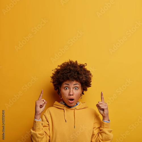 Fotografie, Obraz Wow, look there! Impressed shocked woman with Afro hair points fore fingers abov
