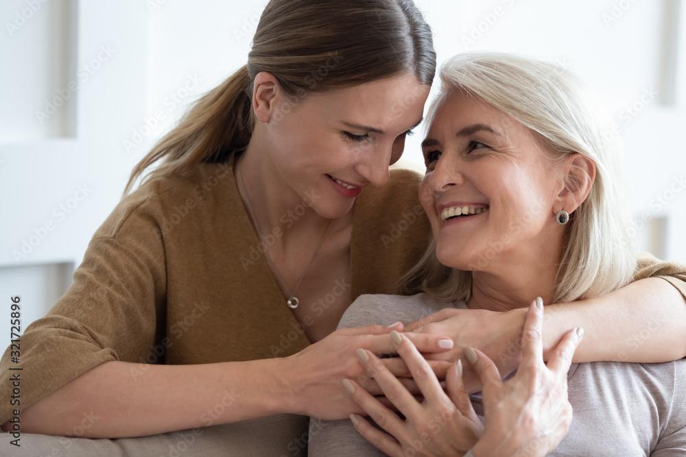Fotografia Adult daughter hug senior mother showing love at home
