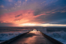 Big Waves Breaking On A Stone Pier In Stormy Weather With A Bright Sunset, A Big Tide. Black Sea. Sochi, February.