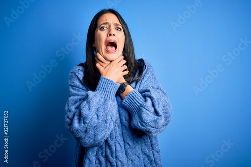 Young brunette woman with blue eyes wearing casual turtleneck sweater shouting suffocate because painful strangle Wallpaper Mural