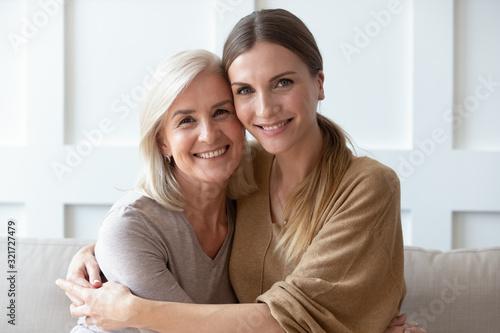 Fototapeta Headshot portrait of mature mom and adult daughter posing obraz