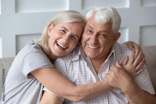Headshot portrait of happy elderly couple embracing