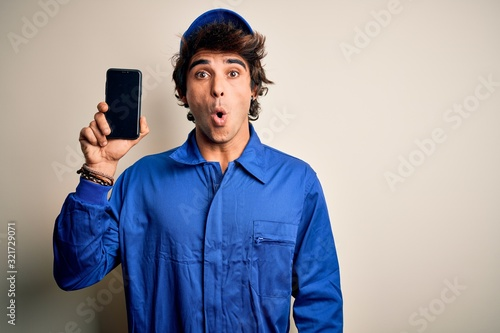 Young mechanic man wearing uniform holding smartphone over isolated white background scared in shock with a surprise face, afraid and excited with fear expression